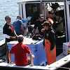 "The National Geographic Channel crew, clockwise from bottom center, Andy Baker, Kory Kozak, an unnamed man, and Bill Roach talk to Capt. Dave Carraro, right, aboard his boat FV-Tuna.com. They were filming video and stills at the Gloucester Marine Railways on Rocky Neck to promote the NatGeo series ""Wicked Tuna."""