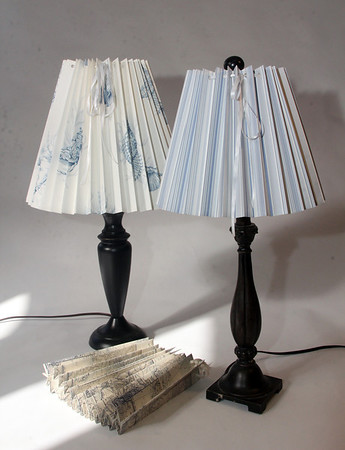 """Clever Covers. These pleated lampshade slipcovers are handmade by Ariana Barron of Rockport, and of La Provence, 4 Main Street, Rockport. They adjust to fit over an existing lampshade of any shape. Two sizes, 12 inches, $26, (left) and 9 inches, $22, (right) with adjustable width. Shade at bottom is folded. Also available at  <a href=""""http://www.shopclevercovers.comPhoto"""">http://www.shopclevercovers.comPhoto</a> by Allegra Boverman."""