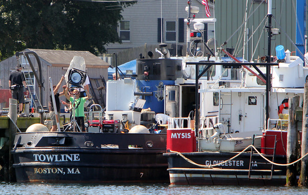 "A National Geographic Channel production film crew sets up its equipment on the Towline, left, tied up at the Gloucester Marine Ralways, in preparation for filming the fishing vessels of ""Wicked Tuna"" on the open sea. Photo by Allegra Boverman."