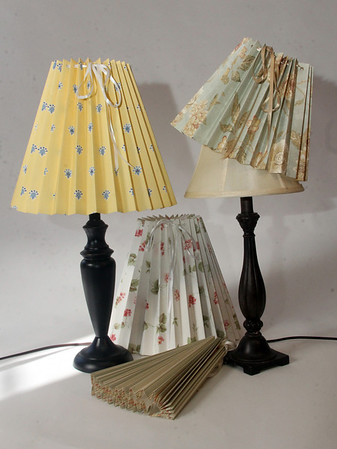 """Clever Covers. These pleated lampshade slipcovers are handmade by Ariana Barron of Rockport, and of La Provence, 4 Main Street, Rockport. They adjust to fit over an existing lampshade of any shape. Two sizes, 12 inches, $26, (left and center back) and 9 inches, $22, (right) with adjustable width. Shade at bottom is folded. Also available at  <a href=""""http://www.shopclevercovers.comPhoto"""">http://www.shopclevercovers.comPhoto</a> by Allegra Boverman."""