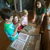 DESI SMITH/Staff photo.  From left to right, Henry Chadbourne 7, Caton Andrade, 4 1/2, and Cecilia Chadbourne 5, try to identifiy different bird bones with help from Cape Ann Consevation intern Nicole Pyser, at the Discovery Center at Ravenswood Park.
