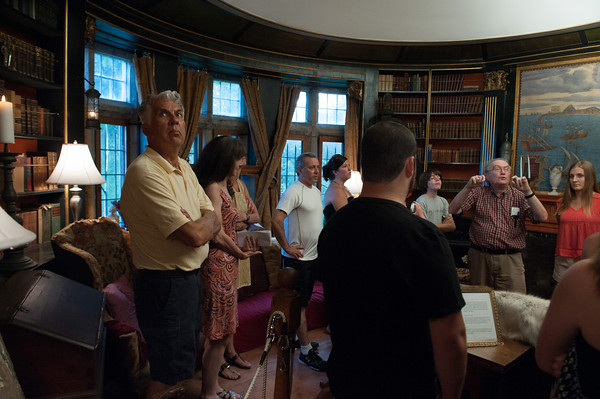 DESI SMITH/Staff photo<br /> John Pettibone, second from right, tells tourists about how the ceilng makes an audible whisper in Hammond Castle's circular library.