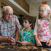 DESI SMITH/Staff photo.  <br /> Alan Braver of Gloucester looks over items found in Ravenswood Park with his grandchildren, Henry Chadbourne, 7, and sister Cecilia, 5, of Rockport, while at Discovery Center at Ravenswood Park.
