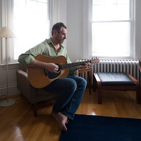 Jim Vaiknoras/Cape Ann Magazine. John Rockwell of Rockport at home with the acoustic guitar he has been playing since his youth.