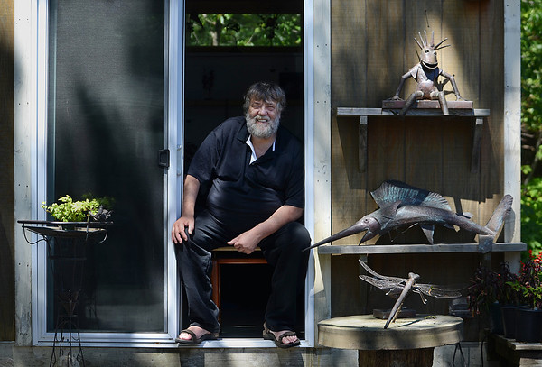 Mike Springer/Cape Ann magazine. Sculptor Bart Stuyf sits at the entrance to his studio on 16 Mussel Point Way, overlooking the ocean in Gloucester.