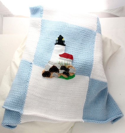 Hand-knit baby blanket with applique of Annisquam Lighthouse. $65. My Sea Baby, 17 Mount Pleasant Street, Rockport. myseababy.com Photo by Allegra Boverman.