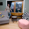 Amanda Thurston of Rockport stands next to her custom-made chair slipcovers, along with the stool she renovated with fabric. She is wearing a belted tunic which, of course, she also made as well as the oversized Ottoman pillow.<br /> <br /> Photo by Jim Vaiknoras.