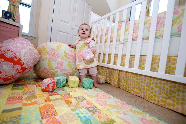 Baby Raegan Currier of Rockport plays with her hand-made baby blocks, standing on her hand-made quilt, and leaning on her hand-made Ottoman pillows, and wearing her handmade dress, all which are the handiwork of Rockport's Amanda Thurston, who founded Pink Armor by Amanda.<br /> <br /> Photo by Jim Vaiknoras.