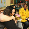 ALLEGRA BOVERMAN/Staff photo. Cape Ann Magazine. Gloucester: Alicia Silas is given a bouquet of roses and is hugged by Trinity O'Leary, 7, child of one of Silas' friends, after the Wellspring House Adult Learning Initiative graduation ceremony on Wednesday evening. Seated next to Silas from left are fellow graduates Elda Rodriguez and Tasha Walker.