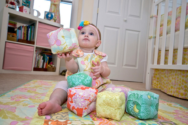 Baby Raegan Currier of Rockport plays with her hand-made baby blocks, sitting on her hand-made quilt and wearing her handmade dress, all which are the handiwork of Rockport's Amanda Thurston of Pink Armor by Amanda.<br /> Photo by Jim Vaiknoras.