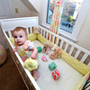 Baby Raegan Currier of Rockport stands in her custom-designed crib featuring hand-made bumpers, blocks, dress, curtains and Ottoman pillows. These are all the handiwork of Rockport's Amanda Thurston.<br /> <br /> Photo by Jim Vaiknoras.