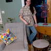 Amanda Thurston of Rockport stands next to her custom-made chair slipcover, along with the stool she redesigned. She is wearing a belted tunic which, of course, she also made.<br /> <br /> Photo by Jim Vaiknoras.