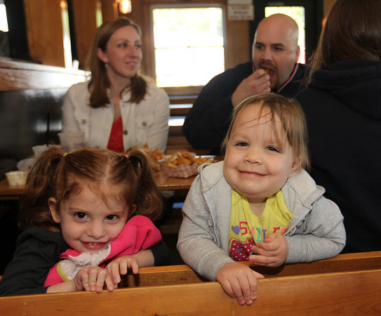 Emma Pietal, 3, left, and Chloe Pecci, 2, at lunch at Woodman's with Alexandra and Brian Pecci behind them. Photo by Allegra Boverman.