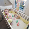 Baby Raegan Currier of Rockport stands in her custom-designed crib featuring hand-made bumpers, blocks, dress, curtains and Ottoman pillows. These are all the handiwork of Rockport's Amanda Thurston.<br /> Photo by Jim Vaiknoras.