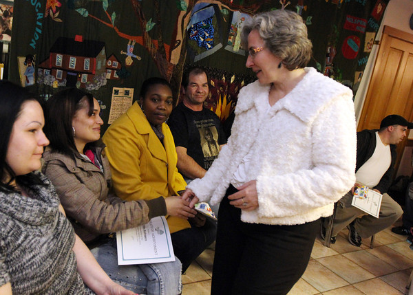 ALLEGRA BOVERMAN/Staff photo. Cape Ann Magazine; Gloucester: Wellspring House President and Executive Director Kay O'Rourke, standing, shakes hands with and congratulates graduates of the Adult Learning Initiative Program during their graduation ceremony on Wednesday evening. From left, seated, are: Alicia Silas, Elda Rodriguez, Tasha Walker, Kevin Hickey, Frederick Rhodes, IV (behind O'Rourke), and Dan Medeiros, far right.