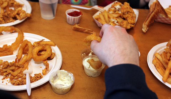 Brian Pecci dips an onion ring in tartar sauce at Woodman's. Photo by Allegra Boverman.