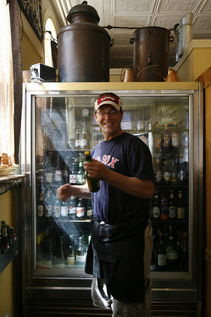 Eric Lorden, owner of Passports, shows several of his favorite beers from their offerings. The restaurant offers over 40 beers. Staff photo/Kate Glass