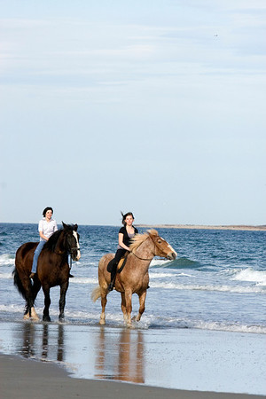Gloucester:  Serena Barbara rides Frank, left, with friend Mariah Place, 14, on Duke on Good Harbor Beach on a warm April evening. Staff photo/Amy Sweeney