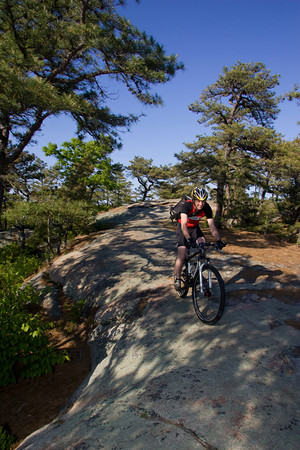 Coley Bryan of Gloucester rides his mountain bikes at the top of Red Rocks in Gloucester. Photo by Mary Muckenhoupt