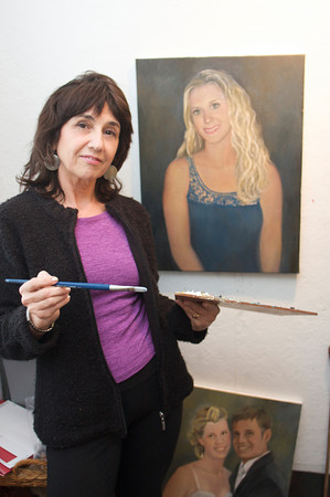 Luisa F.V. Cleaves paints a portrait of Alex Murray in Cleaves' Rockport Gallery. Photo by Mary Muckenhoupt