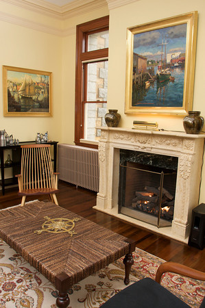 The living room with restored fireplace that was once hidden behind a wall before David and Gail Vastola took the dilapidated Carnegie Library in Rockport and turned it into their home. A Don Mosher painting hangs above the mantel with a Ken Knowles painting hanging left.  Photo by Mary Muckenhoupt