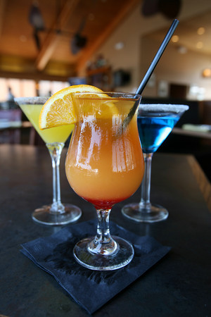 Seaport Grille offers several cocktails, including its signature drink, the Seaport Swizzle, front. Photo by Kate Glass