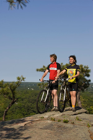 Coley Bryan and his wife Heidi Wakeman of Gloucester take a break from mountain biking and look out over Cape Ann at the top of Red Rocks in Gloucester. Photo by Mary Muckenhoupt