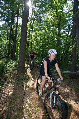 Heidi Wakeman and her husband Coley Bryan bike down a trail at Red Rocks in Gloucester. Experienced bikers, the couple mountain bikes all over Cape Ann. Photo by Mary Muckenhoupt
