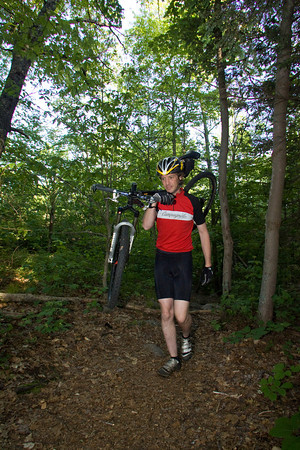Coley Bryan carries his bike over part of the trail on his way to Red Rocks in Gloucester. Photo by Mary Muckenhoupt