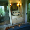 The master bathroom of Joyce Fossa's home has is a solid<br /> egg-shaped dark granite bath tub, a sink made of honey onyx, birdeye maple cabinets, a shower seat made from a slab of the<br /> bluestone used on the living room mantle and the door between the half bath and full bath has pressed sea glass in an arched design.<br /> Photo by Amy Sweeney