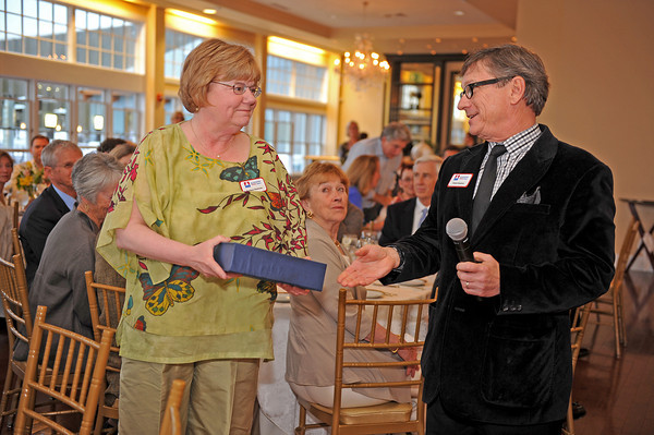 Gloucester, Robert Boulrice treasurer of the Gloucester Stage Company hands Barbara Hargrove a glass plaque at a fundraiser held at Cruiseport May 20,2011 for her many years at the Stage Company,she leaving this year. Desi Smith/Gloucester Daily Times.