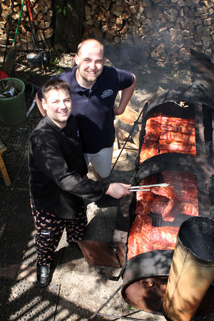 Ryan Cox Executive Chef and co-owner and co-owner of The Farm Bar & Grille<br /> Brad Atkinson show-off the smoker which is located outside behind the kitchen.<br /> Photo by David Le.