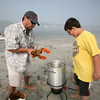 Jake D'Ambrosio, 10, watches as his father Frank gets ready to put a lobster in the pot for the clam bake.<br /> Photo by Amy Sweeney.