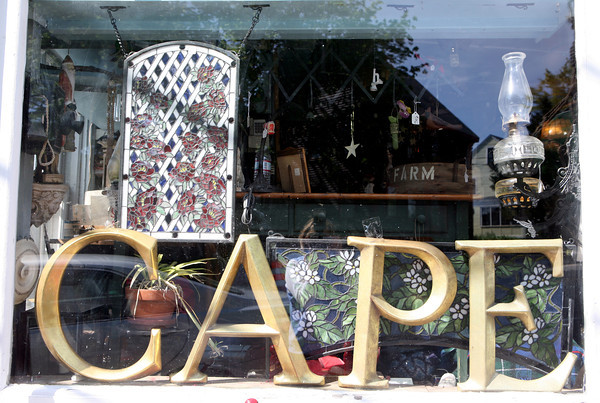 Cather Howard Galli, daughter of business owners Laura and Edwiin Howard of Howard's Flying Dragon Antiques in Essex, found large gold letters and started to write messages in the window display. The sayings caught on and she changes them a few times a week. <br /> Photo by Amy Sweeney.