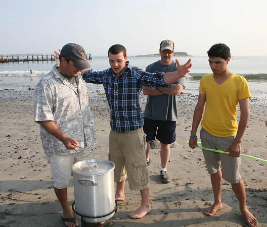Joel D'Ambrosio jokes around with his father, left, as they finish up a clam bake at Magnolia Beach. With him are Tom Cooney and Leo Rivera. <br /> Photo by Amy Sweeney