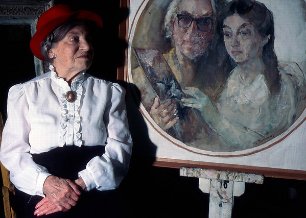Theresa Bernstein poses for her portrait in the late 1980's. She is sitting in front of  a painting done by her husband William Meyerowitz. Photo by Amy Sweeney/Cape Ann Magzine.