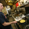 Manchester: Matthew Wallace cooks up a tomato spinach and feta omelet with toast Beach Street Cafe. Photo by Kate Glass/Cape Ann Magazine