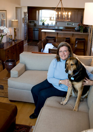 Steel sits in her living room with her daughter's dog Daisy. She had her couch specially designed with a low back to be able to enjoy the view to her kitchen from this angle, or from her kitchen to the deck when she is at the other end of the room. Photo by Amy Sweeney
