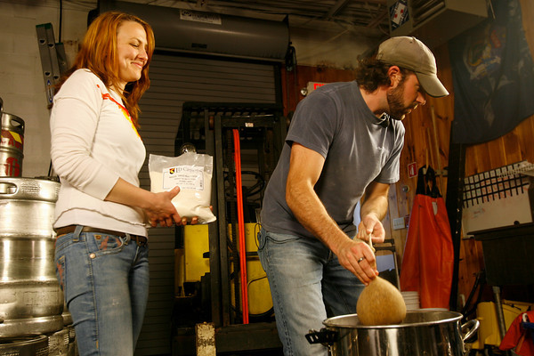 Kate Lynch holds a bag of malt as T.J. Peckham removes a bag of specialty grains from the wort.<br />  Photo by Kate Glass