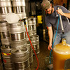 T.J. Peckham gets the carboy ready for racking, which separates the liquid from the yeast after the primary fermentation process.<br />  Photo by Kate Glass