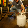 T.J. Peckham turns off the gas after cooking the wort.<br />  Photo by Kate Glass