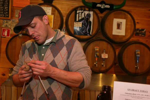 Dylan L'Abbe-Lindquist, General Manager of Cape Ann Brewing Co., knitting at the Cape Ann Brewery. Photo by Kate Glass