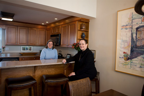 Suzanne Carver, interior designer,  and June Steel, sit at the granite counter in Steel's kitchen. The two selected this bench seats to provide an unobstructed view from the kitchen to the deck. Photos by Amy Sweeney