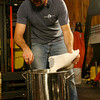 T.J. Peckham adds malt to the wort.<br />  Photo by Kate Glass