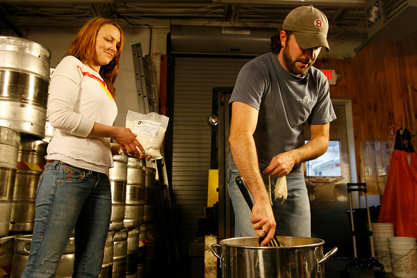Kate Lynch holds a bag of malt as T.J. Peckham stirs the wort.<br />  Photo by Kate Glass