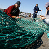 Gloucester: Joe Dimaio, Shawn Grasso, and Gus Margiotta repair fishing nets for the Princess Laura on the State Fish Pier yesterday afternoon. Photo by Kate Glass/Gloucester Daily Times Monday, October 27, 2008