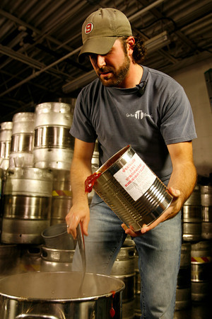 T.J. Peckham adds strawberry rhubarb preserves to the wort.<br />  Photo by Kate Glass