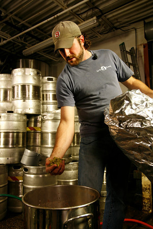 T.J. Peckham adds hops to the brew.  Photo by Kate Glass