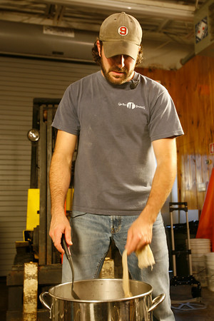 T.J. Peckham removes a bag of specialty grains from his batch of strawberry rhubarb beer.  Photo by Kate Glass