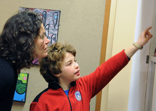 Gloucester: Heidi Wakeman and her son Owen Bryan 9, look over some photos and art work done by Jason Burroughs and Cole Herbst at Cruiseport to support Art Haven's after school programs.Desi Smith/Gloucester Daily Times.  January 28,2011.